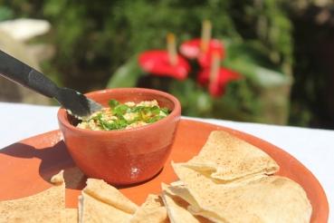 Típica pasta árabe de grão-de-bico. Na foto, decorada com cebolinha e páprica picante